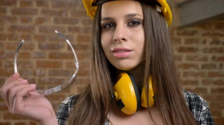 pedreiro : Young pretty attractive women in helmet looking straight into camera, holding and biting her glasses, female builder, brick background, closeup