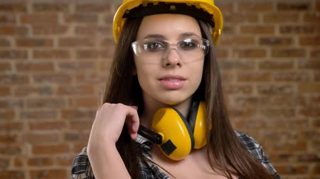 pedreiro : Young pretty attractive women in helmet, headphones and glasses looking straight into camera and touching her long hair, female builder, brick background, closeup