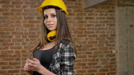 pedreiro : Beautiful attractive young women in helmet and headphones looking straight into camera and holding wrench, smiling, female builder, brick background
