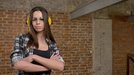 pedreiro : Beautiful attractive young women in glasses and headphones confidently looking into camera and crossing hands, female builder, brick background