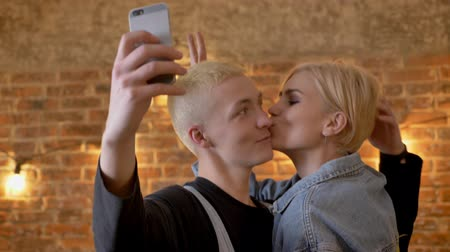 yanak : Young attractive couple of hipsters makes selfie on smartphone, and fools around, communication conception, brick background Stok Video