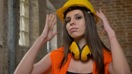 brick factory : Young pretty attractive women in helmet and earphones looking in camera, touching and adjusting casque, crossing hands, female builder, brick building background Stock Footage