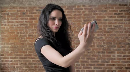 bochechudo : Young charming brunette girl is making selfie on her smartphone, communication conception, brick background Vídeos