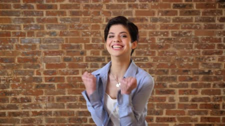 feminist : Young short hair girl is incredibly happy because of victory, emotion conception, brick background Stock Footage