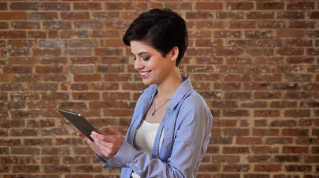 feminist : Young beautiful girl is typing message on her tablet, comunication concept, brick background
