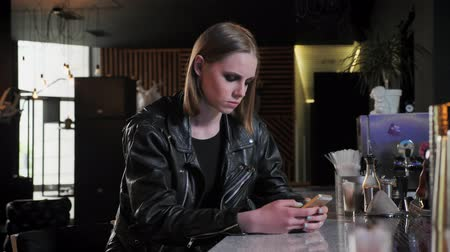 pankáč : Young beautiful women in black jacket with heavy make up sitting and texting on phone, serious, bar background Dostupné videozáznamy