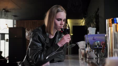 ivászat : Young beautiful women in black jacket with heavy make up drinking wine and looking forward, complicated, bar background Stock mozgókép