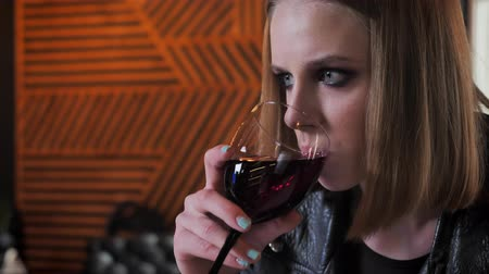 rocker : Young beautiful women in black jacket with heavy make up drinking wine, determined, cafe background