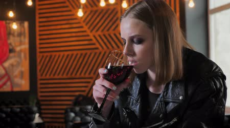 ivászat : Young pretty women in black jacket with heavy make up sitting and drinking wine, stern, cafe background