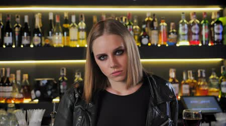 ivászat : Young beautiful women in black jacket with heavy make up looking straight in camera, stern, determined, bar background Stock mozgókép