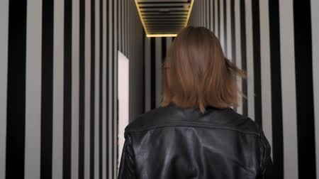 rocker : Young beautiful women with heavy make up in black jacket inviting you and walking away, striped corridor background Stock Footage