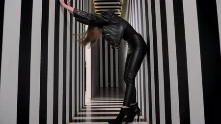 rocker : Young beautiful women in black leather clothes dancing, shaking head and sitting down, striped corridor background