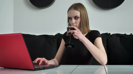 ivászat : Young beautiful women with heavy make up using laptop and drinking wine, smiling, black and white cafe background