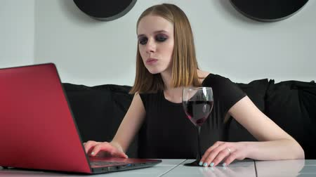 строгий : Young beautiful women with heavy make up using laptop and drinking wine, determined, black and white cafe background