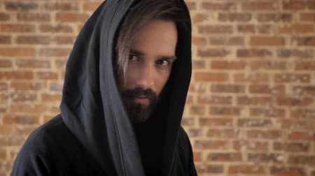 привлекать : Young interesting man with beard in hood is watching at camera, goes away, brick background