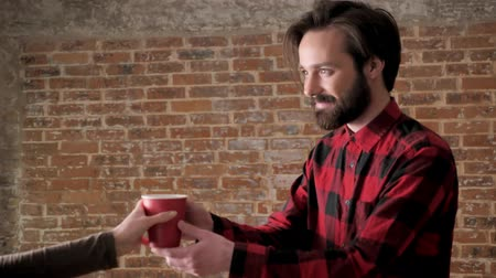 sincerely : Young attractive man with beard gives cup of tea to girl, communication concept, brick background Stock Footage