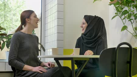 discurso : Two young beautiful womans sitting in cafe, one of them pretty muslim woman in hijab, talking and laughing