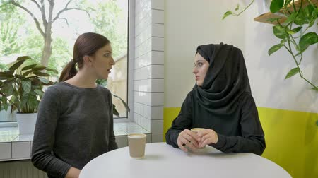 saying : Two young beautiful womans sitting in cafe, one of them muslim woman in hijab telling something to other woman Stock Footage