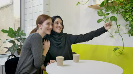 İslamiyet : Two young pretty womans sitting in cafe, one of them muslim woman in hijab taking selfie with phone and posing, smiling
