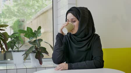 multikulturní : Young beautiful muslim woman in hijab drinking coffee and smiling, sitting in cafe