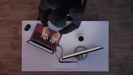 server room : Young man in black hoodie sitting behind desk, typing on laptop and then running away when lights turn on during night, top shot