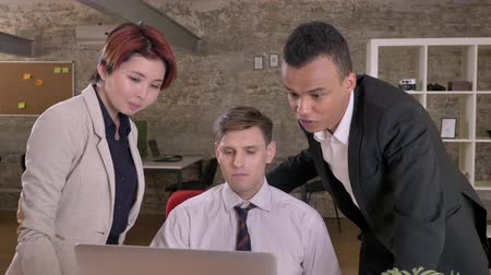 multikulturní : Young business black man speaking and pointing at laptop when caucasian man and asian woman listening him in modern office