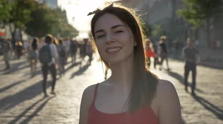 ruivo : Portrait of young beautiful woman with ginger hair standing on street, looking in camera and smiling, people walking around