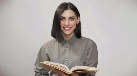 rty : Young pretty woman with short brown hair holding book and reading, then looking in camera and smiling, white background Dostupné videozáznamy