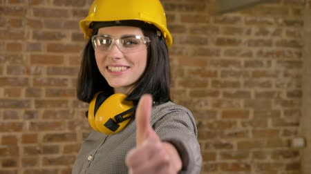 Young beautiful builder woman standing, looking in camera and showing big thumbs-up, smiling, brick background, circling around view