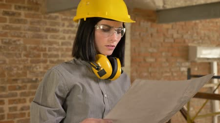 brick factory : Young charming architect woman holding paper and looking forward, concentrated, brick building background Stock Footage