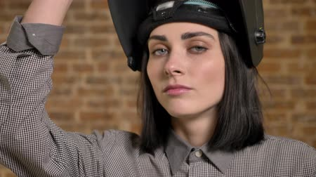 Young beautiful women with short brown hair looking into camera, lifting her helmet, female builder, brick building background