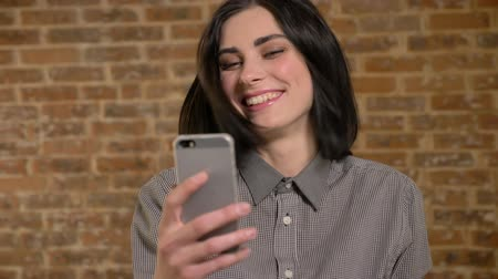 Young beautiful woman with short brown hair looking at phone and laughing, brick wall background