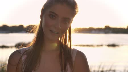 Portrait of young charming woman looking in camera and laughing, sunset and lens flare, river and nature background Vídeos