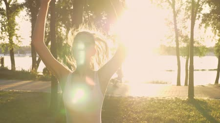 Young woman doing star exercise in park, weight loss, fitness model jumping, other woman running on back, lens flare, beautiful view