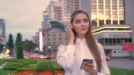Young beautiful serious girl is typing message on her smartphone at sunset in city center in summer, thinking process, communication concept