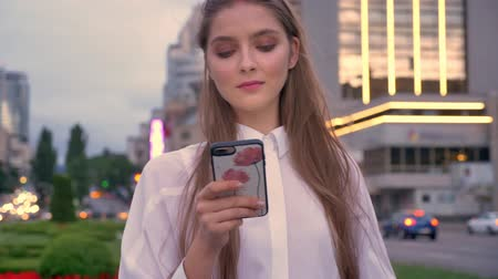 Young cute girl is watching on her smartphone at sunset in city center in summer, thinking concept, communication concept Vídeos