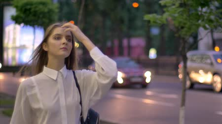 Young beautiful confident girl is going through sreet in evening in summer, thinking conception, walking conception Stock Footage