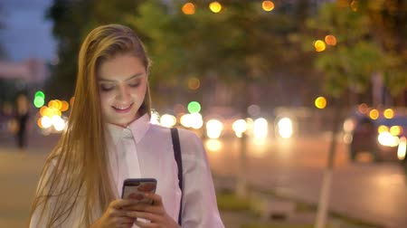Young attractive interested girl is typing message on her smartphone in evening in summer, smiling, communication concept Stock Footage