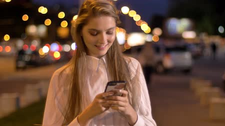 Young attractive girl is typing message on her smartphone in evening in city center in summer, communication concept