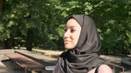 Young attractive muslim girl in hijab walks up stairs in park in daytime in summer, smiling, crossing street, religious concept, urban concept, side view Vídeos