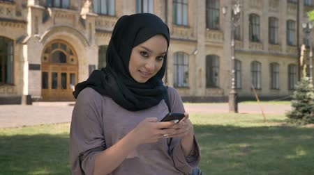 truly : Young sweet muslim girl in hijab is typing message on smartphone in daytime in summer, giggling, building on background, religiuos concept, communication concept