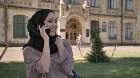 sincerely : Young sweet muslim girl in hijab is talking on phone and laughing in daytime in summer, building on background, religiuos concept, communication concept Stock Footage