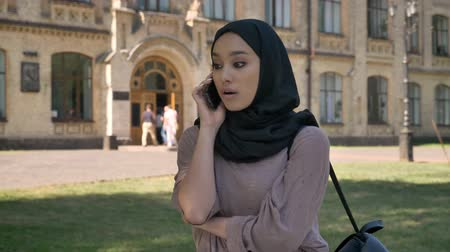 sincerely : Young sweet muslim girl in hijab is talking on phone and hand up in daytime in summer, building on background, religiuos concept, communication concept