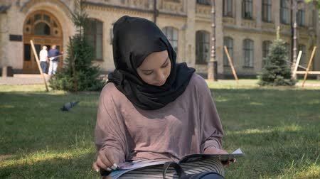 ilginç : Young muslim girl in hijab is sitting on lawn and reading magazine, builging on background, religious concept, relax concept Stok Video