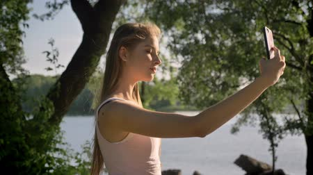 dospělí : Young pretty woman with long hair taking selfie with her phone and smiling, park near river background, beautiful view