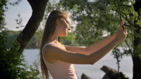 Young pretty woman taking selfie with her phone, looking in camera and smiling, standing in park near river Stock Footage