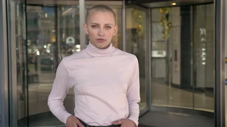 Young extraordinary bold girl is standing with hands on hips, staring at camera, revolving doors on background, urban concept Stock Footage