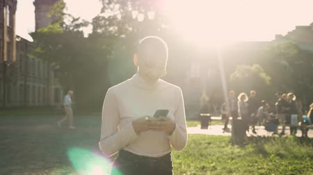young extraordinary bold girl is walking through park in daylight, in summer, watch message on smartphone, smiling, communication concept Stock Footage