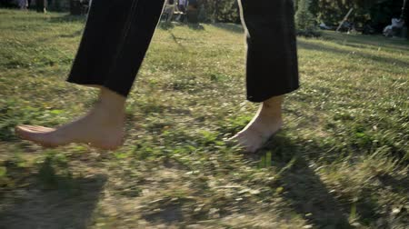 Legs of women walk on grass in park in daytime in summer, healthy lifestyle Stock Footage