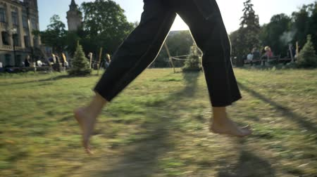 Legs of women run on grass in park in daytime in summer, healthy lifestyle, blured background Stock Footage